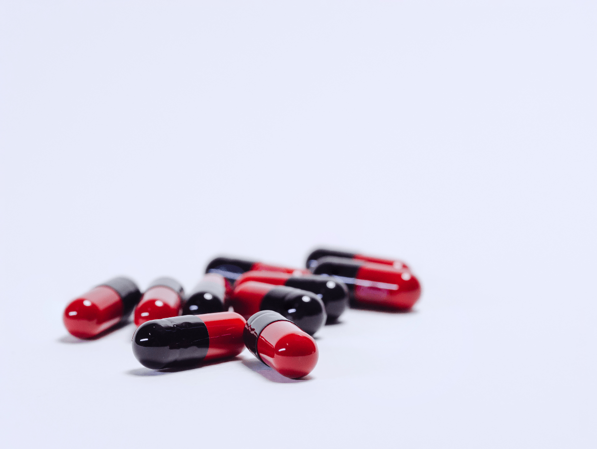 Red and black Ampicillin pills for dogs and cats.