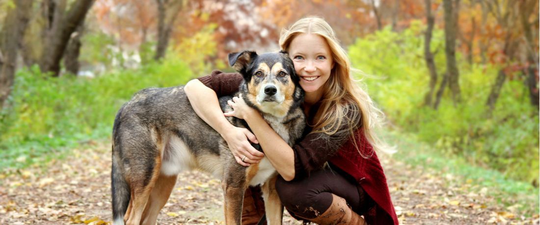 A woman and her dog stop for a hug on a leafy trail.