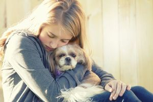 A sad teenager hugs her dog.