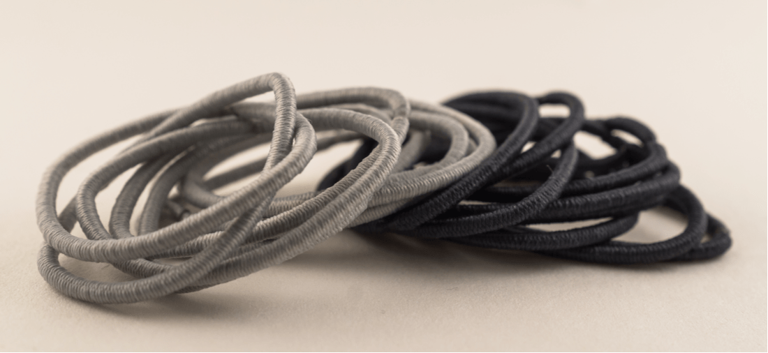 A pile of black and grey hair ties.