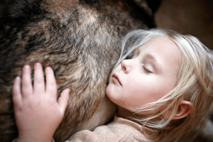 A child rests with her head against a dog's fur.