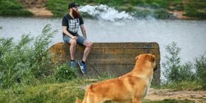 A man exhales a vape cloud while a dog watches from a distance.